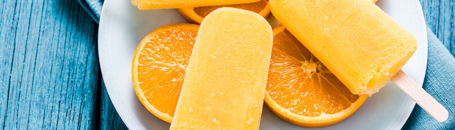 Orange slices and popsicles in a white plate on a blue wood table